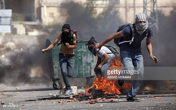 Masked Palestinians take cover before to throw stones toward Israeli soldiers near the Jewish West Bank settlement Beit El north of Ramallah on...