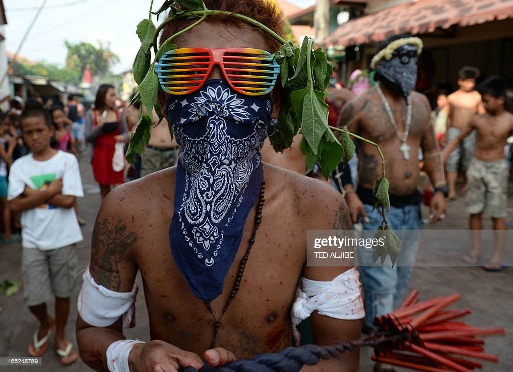 A masked penitent flagellates himself as part of Lenten observance in Angeles City, Pampanga province, north of Manila on April 17, 2014. The dominant Roman Catholic church does not condone flagellation and other extreme acts of penitence including gory Good Friday reenactments of the crucifixion of Jesus Christ, but devout Catholics say it is a means of atoning for their sins and to implore God to spare them and other members of their families from illness or bad luck.