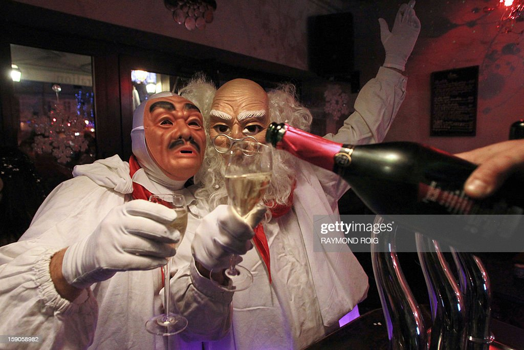 Masked people toast with Blanquette de Limoux, a local sparkling wine, in the historical centre of Limoux, southern France, on January 6, 2013, as they take part in the city's carnival, which started on January 6 and will end on March 17. AFP PHOTO / RAYMOND