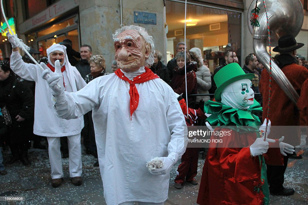 Masked people walk in the historical centre of Limoux, southern France, on January 6, 2013, as they take part in the city's carnival, which started on January 6 and will end on March 17. AFP PHOTO / RAYMOND