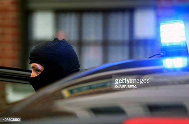 A masked police officer arrives on the scene in Alsdorf near Aachen western Germany after three arrests were made on Novermber 17 2105 German police...
