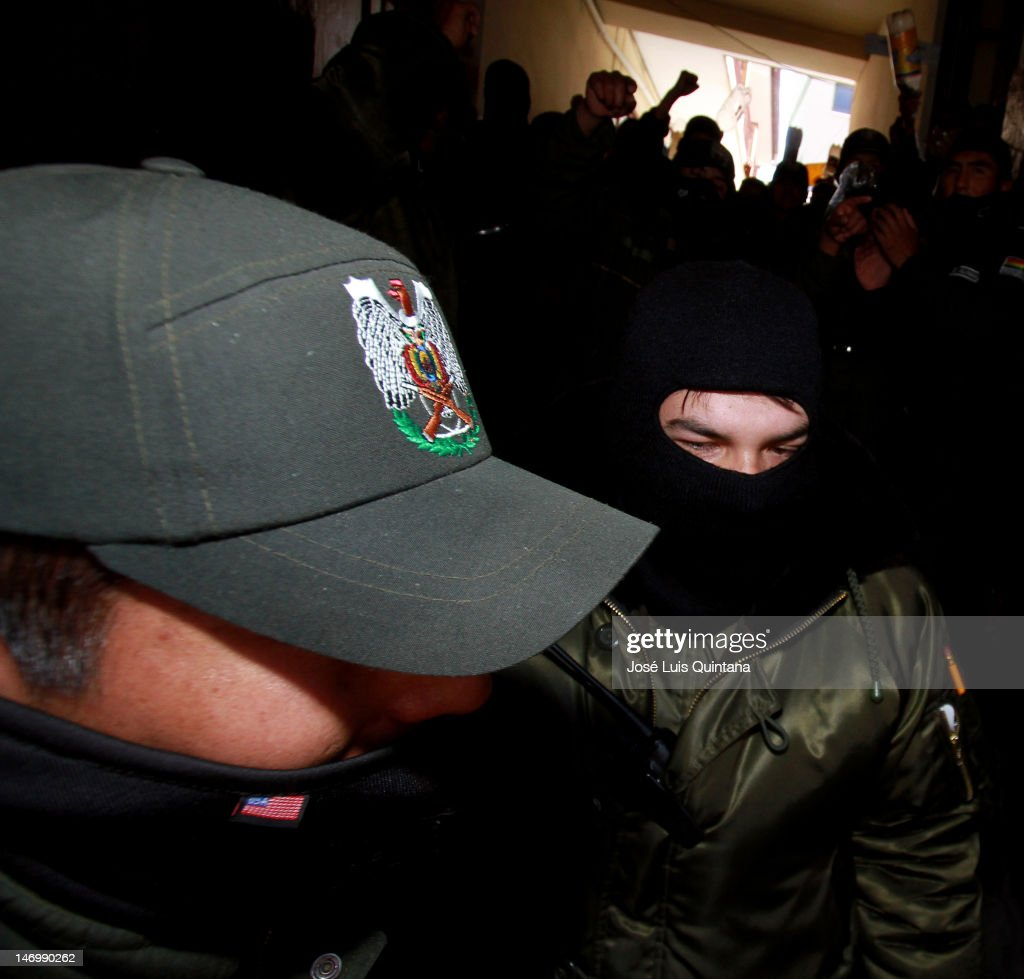 Masked police portest oustside the Goverment Palace, guarded by soldiers, during the 4th day of strike in protest of low pay, on June 24, 2012 in La Paz, Bolivia. They demand they pay be raised to equal that of soldiers of the same rank.