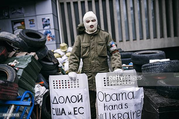 A masked ProRussia supporter stands guard outside the headquarters of Ukraine's security agency building in the eastern Ukrainian city of Lugansk on...