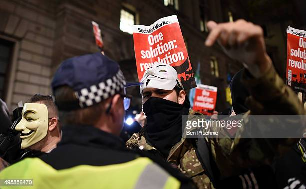 A masked protester argues with police during the Million Mask March on November 5 2015 in London England The annual antiestablishment protest is...