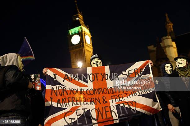 A masked protester holds a flag outside the Houses of Parliament during the Million Mask March on November 5 2014 in London England protesters with...