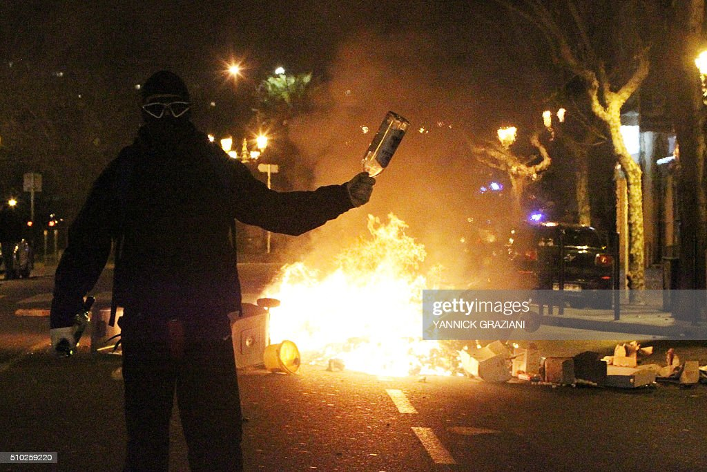 A masked protester holds a glass bottle near burning trash bins on February 14, 2016, in Bastia, on the French Mediterranean island of Corsica, after incidents broke out during a gathering in support of a Sporting Club de Bastia supporter who was injured the previous night in Reims in clashes with police in the city centre following a French L1 football match between Reims and Bastia. / AFP / YANNICK GRAZIANI