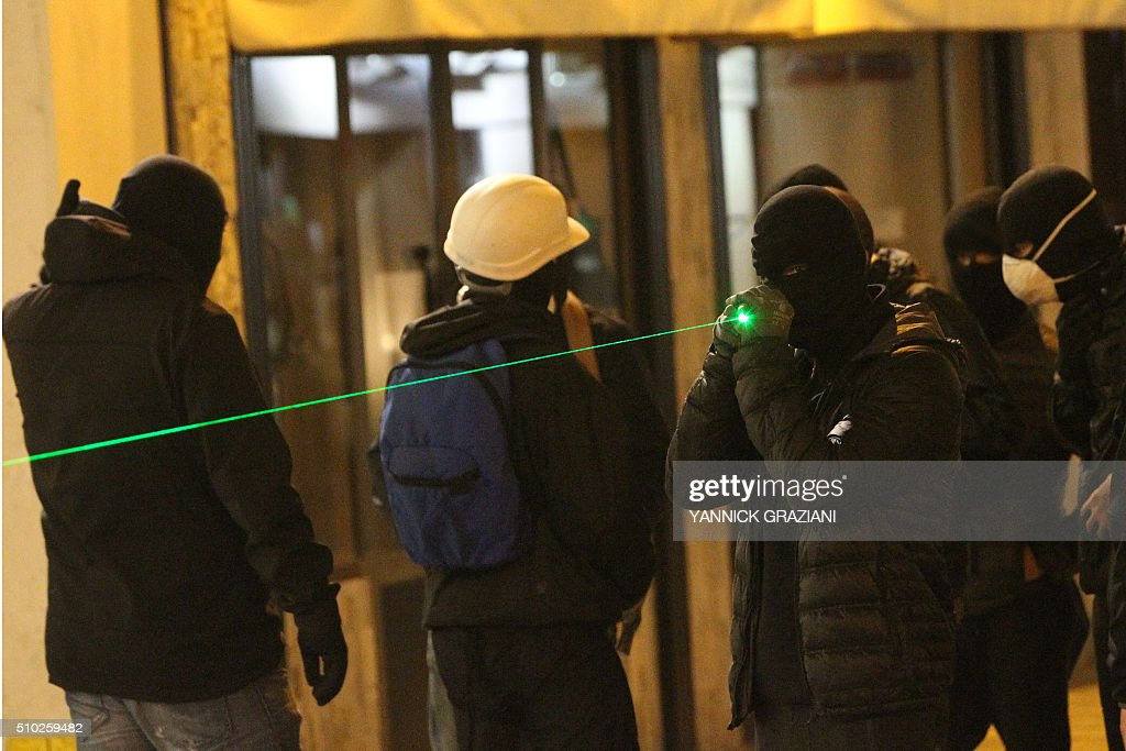 A masked protester holds a laser pointer on February 14, 2016, in Bastia, on the French Mediterranean island of Corsica, after incidents broke out during a gathering in support of a Sporting Club de Bastia supporter who was injured the previous night in Reims in clashes with police in the city centre following a French L1 football match between Reims and Bastia. / AFP / YANNICK GRAZIANI