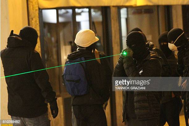 A masked protester holds a laser pointer on February 14 in Bastia on the French Mediterranean island of Corsica after incidents broke out during a...