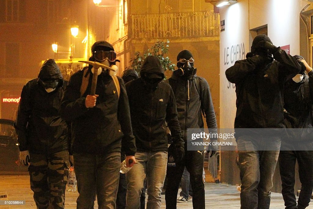 A masked protester holds a picket as he walks with others on February 14, 2016, in Bastia, on the French Mediterranean island of Corsica, after incidents broke out during a gathering in support of a Sporting Club de Bastia supporter who was injured the previous night in Reims in clashes with police in the city centre following a French L1 football match between Reims and Bastia. / AFP / YANNICK GRAZIANI