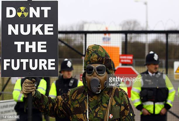 A masked protester holds a placard at the gates to the Hinkley Point nuclear power station as demonstrators gather to mark the first anniversary of...