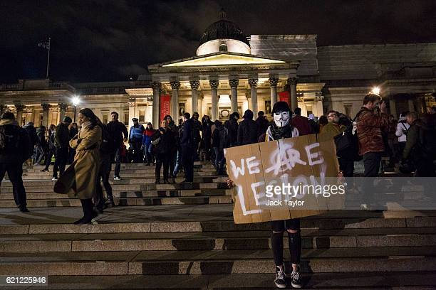 A masked protester holds a sign which reads 'We Are Legion' in Trafalgar Square during the Million Mask March on November 5 2016 in London England...