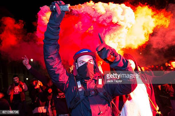 A masked protester holds up a flare on Whitehall during the Million Mask March on November 5 2016 in London England Thousands of demonstrators many...