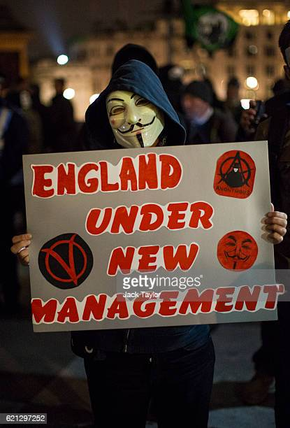 A masked protester holds up a placard in Trafalgar Square during the Million Mask March on November 5 2016 in London England Thousands of...