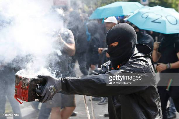 A masked protester launches fireworks in the direction of riot police during a protest on July 7 2017 in Hamburg northern Germany where leaders of...
