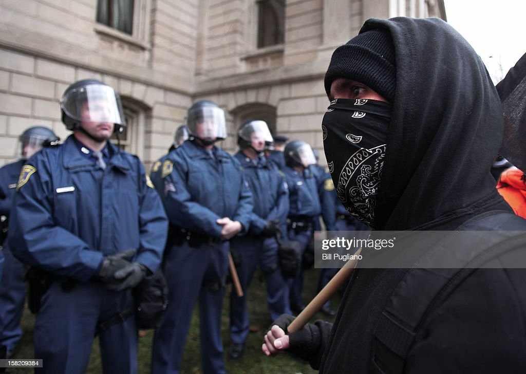 A masked protester looks at Michigan State Police in riot gear as union members from around the country rally at the Michigan State Capitol to protest a vote on Right-to-Work legislation December 11, 2012 in Lansing, Michigan. Republicans control the Michigan House of Representatives, and Michigan Gov. Rick Snyder has said he will sign the bill if it is passed. The new law would make requiring financial support of a union as a condition of employment illegal.