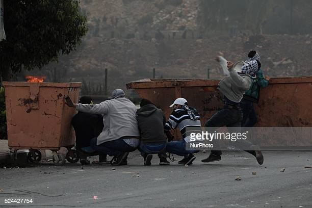 Masked protester reacts in throwing stones towards Israeli army whereas other protesters hiding behind a trash container during a clashes near Beit...