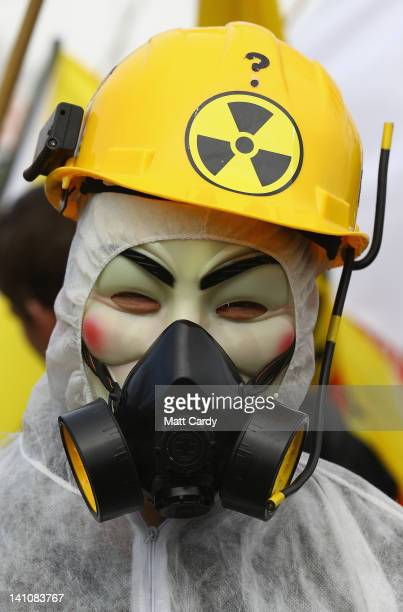 A masked protester stands in front of the gates to the Hinkley Point nuclear power station as demonstrators gather to mark the first anniversary of...