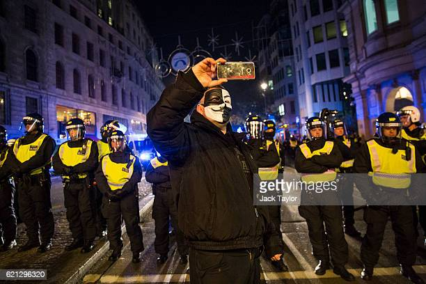 A masked protester takes a selfie in front of a line of police during the Million Mask March on November 5 2016 in London England Thousands of...