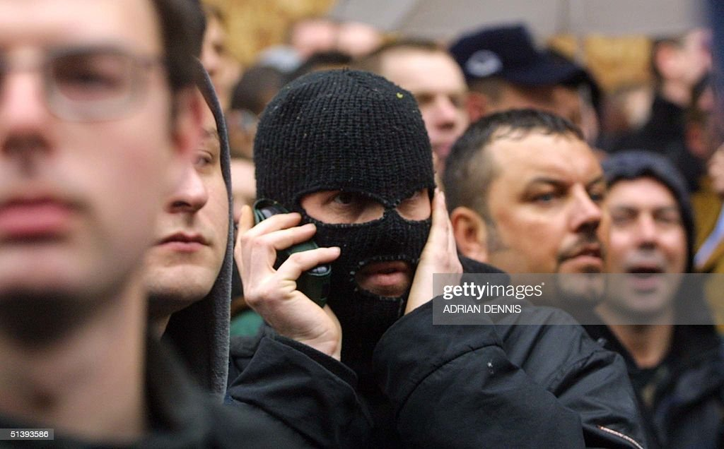 A masked protester talks to other demonstrators on a mobile phone in Oxford Circus during the May Day protests in Central London in London 01 May 2001. The protest dubbed the May Day Monopoly, based on the board game, brought many demonstrators to the streets of the capital to protest against capitalism, and the worsening of the world's environment.
