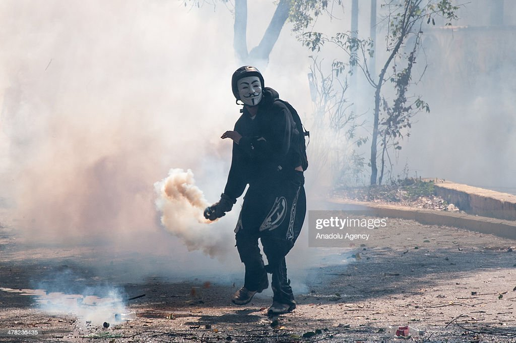 A masked protester throws back a tear gas canister at National Bolivarian Guard members during the anti-government protests in Caracas, Venezuela on March 12, 2014. Three people including a university student and a National Guard member, were shot death and several others injured on Wednesday during the anti-government protests in Venezuela.