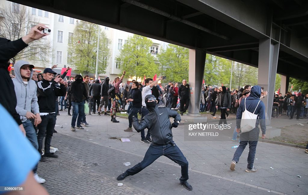 Masked protester throws stones at police after the traditional 'Revolutionary' May Day demonstration in Berlin, on May 1, 2016. Thousands of leftists, trade unionists and workers took to the streets of the capital on the occasion of International labour day. / AFP / dpa / Kay Nietfeld / Germany OUT