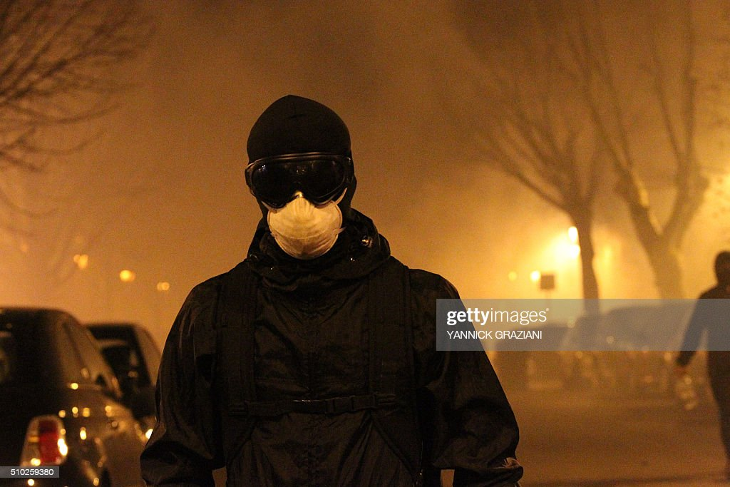 A masked protester walks in the street on February 14, 2016, in Bastia, on the French Mediterranean island of Corsica, after incidents broke out during a gathering in support of a Sporting Club de Bastia supporter who was injured the previous night in Reims in clashes with police in the city centre following a French L1 football match between Reims and Bastia. / AFP / YANNICK GRAZIANI