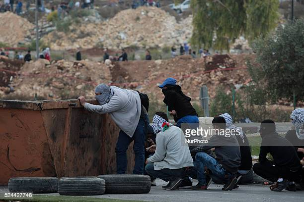 Masked protester watching Israeli army movements while the other protesters are hiding behind a trash container to protect them from Israeli army...