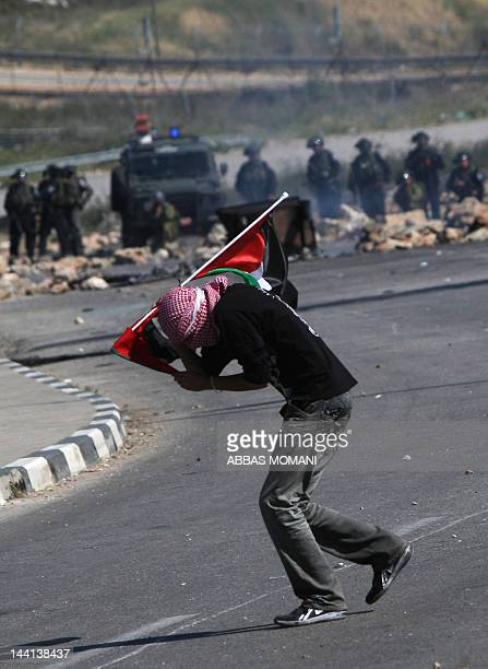 A masked protester waves a Palestinian flag iduring confrontations with Israeli troops outside the Ofer Prison close to the West Bank city of...