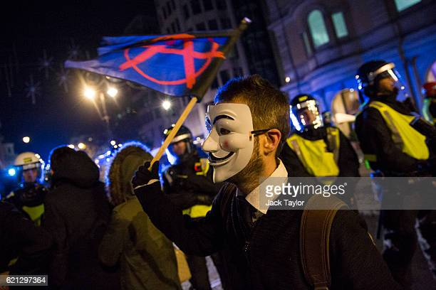 A masked protester waves an 'Anarchy' flag in front of a line of police during the Million Mask March on November 5 2016 in London England Thousands...