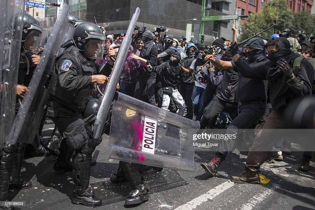 Masked protesters clash with riot police during a march on September 01, 2013. Groups protesting against the proposed energy and education reforms, marching towards the national congress as Mexican president Enrique Pena Nieto sends his Interior Minister to congress to deliver the written version of his first State of the Nation in Mexico City, Mexico.