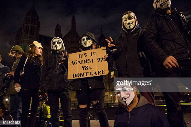 Masked protesters gather outside the Houses of Parliament during the Million Mask March on November 5 2016 in London England Thousands of...
