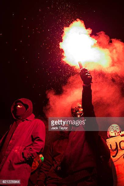 Masked protesters hold a flare as they stand on Nelson's Column during the Million Mask March on November 5 2016 in London England Thousands of...