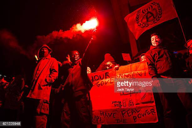 Masked protesters hold banners and flares as they stand on Nelson's Column during the Million Mask March on November 5 2016 in London England...