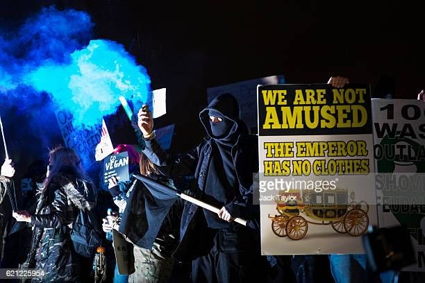Masked protesters hold placards and flares as they stand on Nelson's Column during the Million Mask March on November 5 2016 in London England...