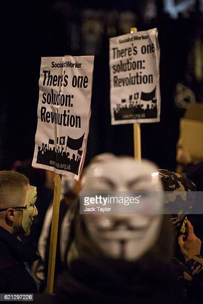 Masked protesters hold up placards outside the Houses of Parliament during the Million Mask March on November 5 2016 in London England Thousands of...