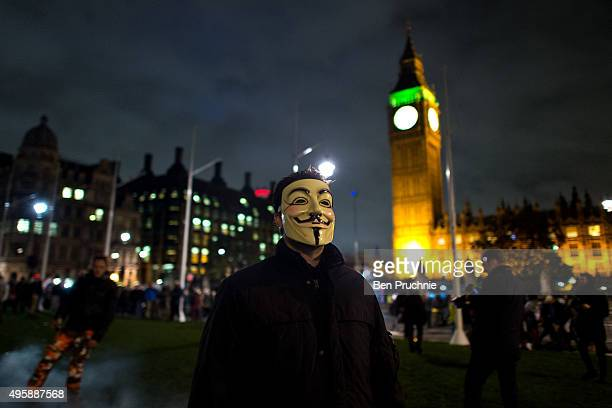 Masked protesters pass in front of the Houses of Parliament during the Million Mask March on November 5 2015 in London England The annual...