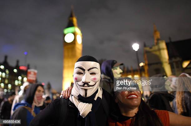 Masked protesters pose in front of the Houses of Parliament during the Million Mask March on November 5 2015 in London England The annual...