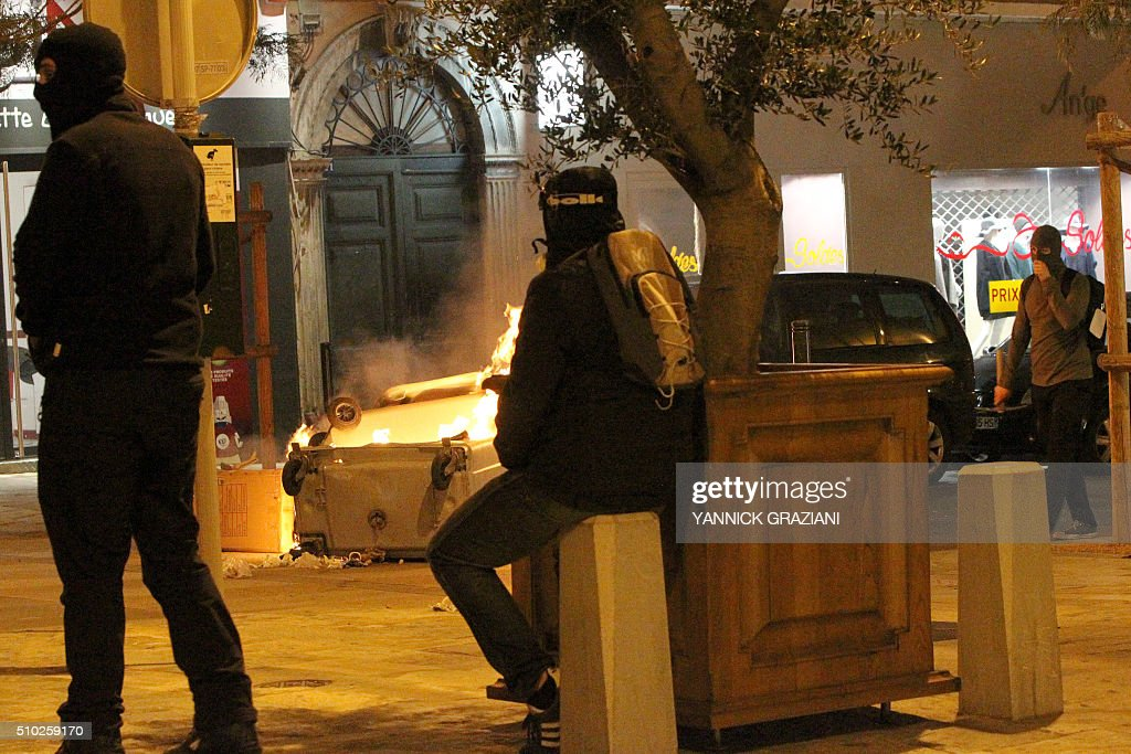 Masked protesters stand near a burning trash bin on February 14, 2016, in Bastia, on the French Mediterranean island of Corsica, after incidents broke out during a gathering in support of a Sporting Club de Bastia supporter who was injured the previous night in Reims in clashes with police in the city centre following a French L1 football match between Reims and Bastia. / AFP / YANNICK GRAZIANI
