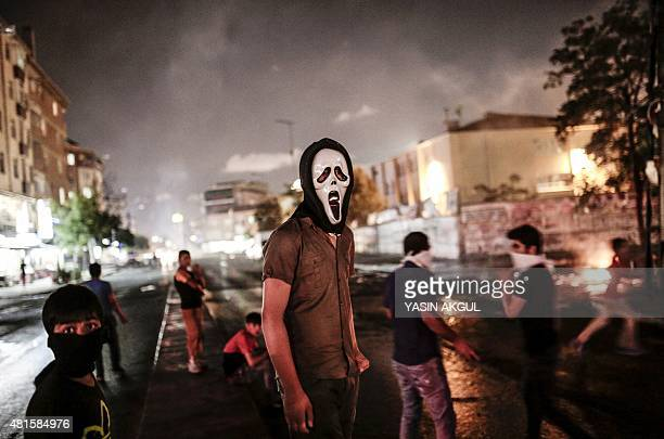 Masked protesters stand on the street in the Gazi district of Istanbul on July 22 2015 two days after a suicide bomb attack killed at least 31 people...
