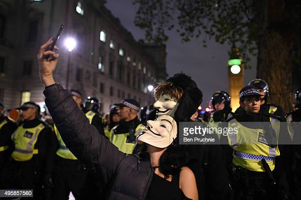 Masked protesters take a selfie in front of the Houses of Parliament during the Million Mask March on November 5 2015 in London England The annual...