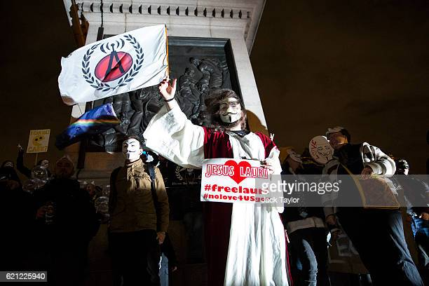Masked protesters wave flags and hold placards as they stand on Nelson's Column during the Million Mask March on November 5 2016 in London England...