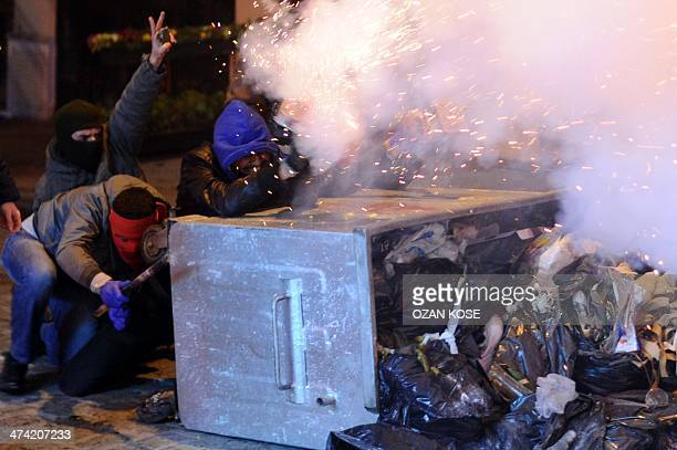 Masked protestors shoot fireworks toward Turkish riot police during a demonstration against new legislation tightening control of the Internet on...