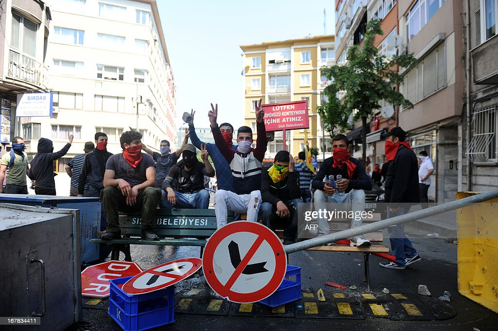 Masked protestors sit on a makeshift barricade flashing V-signs during clashes at a May Day demonstration on May 1, 2013 in Istanbul. Turkish riot police used water cannon and tear gas on Wednesday in a bid to disperse hundreds of protesters who defied a Labour Day ban on demonstrations in a central part of Istanbul. The ban was imposed to avoid trouble during renovation work taking place at the symbolic Taksim square, a traditional rallying point.