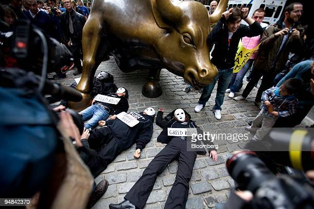 Masked protestors take part in a demonstration in front of the charging bull statue on Broadway near Wall Street in New York US on Thursday Sept 25...