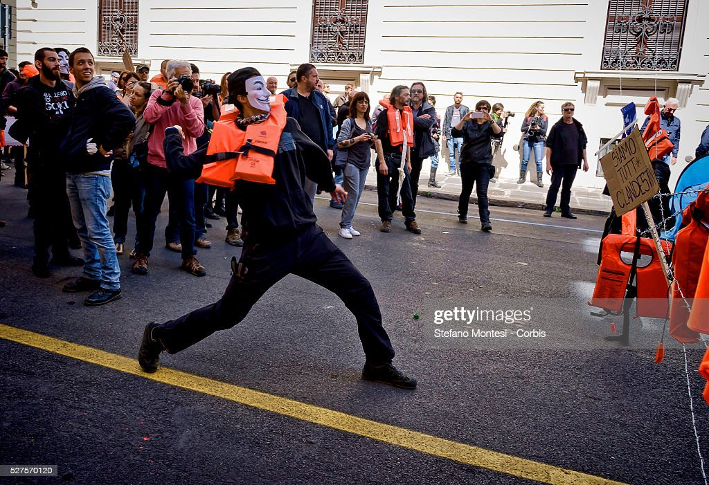 Masked protestors throw eggs as over a thousand demonstrators march in protest against the recent EU migrant agreements made between the Turkish government and the European Union and in support of 'No Borders' and freedom of human movement near the Turkish embassy on May 1, 2016 in Rome, Italy. Police closed roads around the embassy as protestors donned life jackets and created camps of tents surrounded by barbed wire.