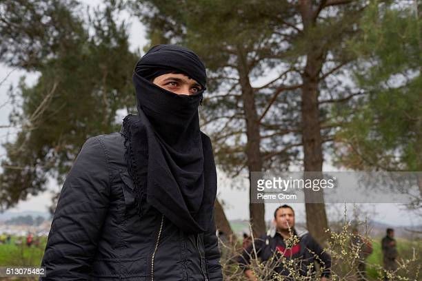 A masked refugee eyes the GreekMacedonia border after clashes with Macedonian forces on February 29 2016 in Idomeni Greece A group of refugees forced...