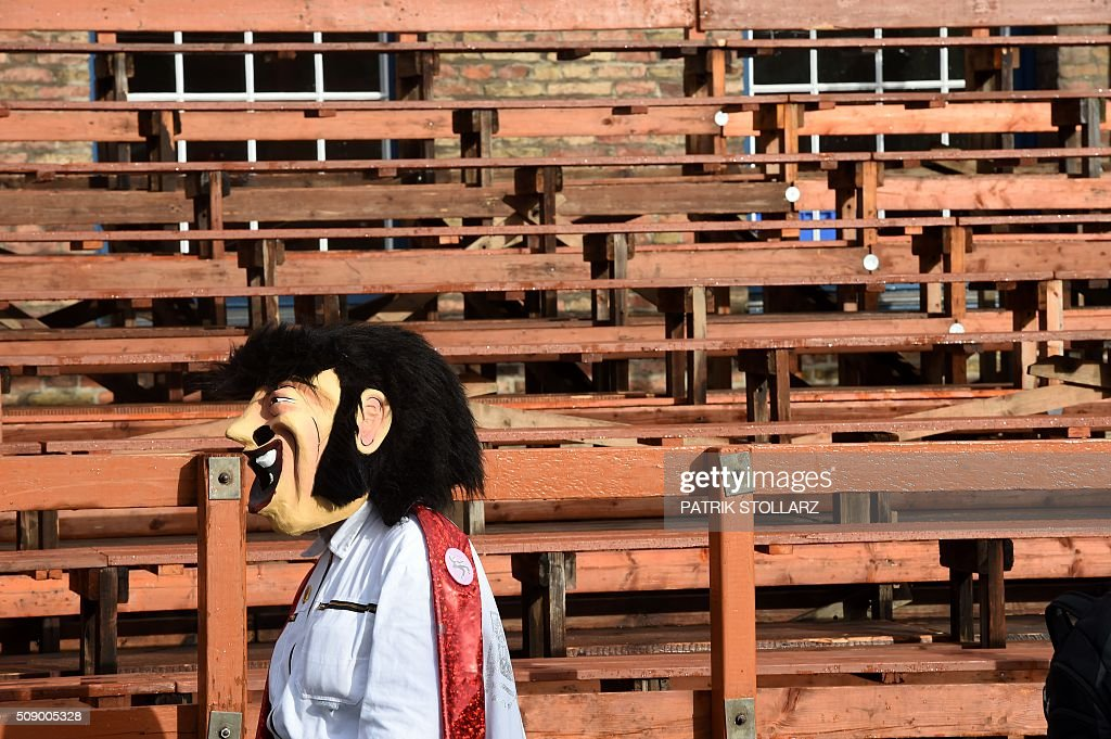A masked reveller walks past the empty stands in front of the city hall in Duesseldorf, western Germany, after the Rose Monday (Rosenmontag) street parade has been cancelled on February 8, 2016. Traditional Rose Monday carnival parades in several western German cities have been cancelled due to stormy weather. / AFP / PATRIK STOLLARZ