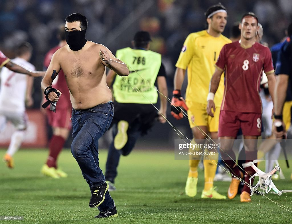 A masked Serbian supporter pulls a drone after a flag with Albanian national symbols was flown over the pitch and pulled down by Serbia's players...