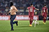 A masked Serbian supporter pulls a drone after a flag with Albanian national symbols has been flown into the stadium during the Euro 2016 group I...