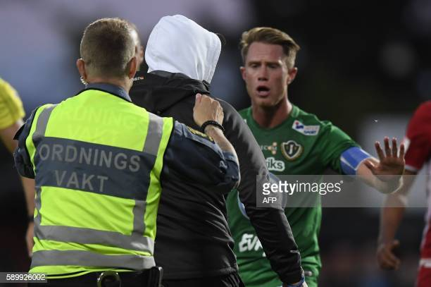 A masked soccer spectator is evacuated from the pitch after he attacked Ostersund's goalkeeper Aly Keita during a football match between Jonkoping...